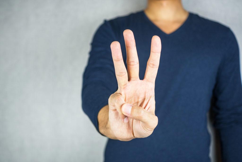 指で3を表している写真